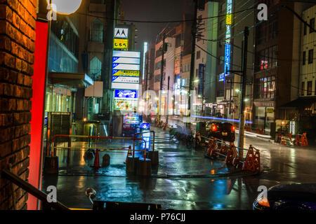 A rainy, moody urban street scene at night, Omiya, Japan - Stock Photo