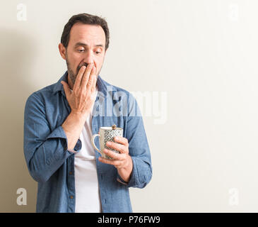 Senior man drinking coffee in a mug cover mouth with hand shocked with shame for mistake, expression of fear, scared in silence, secret concept - Stock Photo