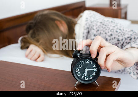 Young woman girl turns off alarm clock waking up in the morning from a call. Unrecognizable student do not want to wake up early for school or univerc - Stock Photo