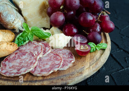 Board with mediterranean appetizers, tapas or antipasti. Assorted Italian style banquet food set. Delicious snack on party. Chopping board with salami - Stock Photo