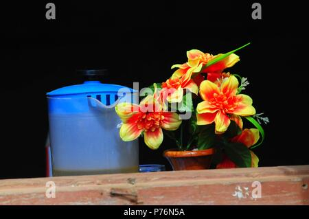 Artificial flowers in a ceramic pot and a plastic watering can stand on a windowsill like a still life in Siem Reap, Cambodia - Stock Photo