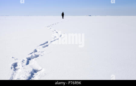 Footsteps of lonely person walking on frozen Baltic Sea covered with snow - Stock Photo
