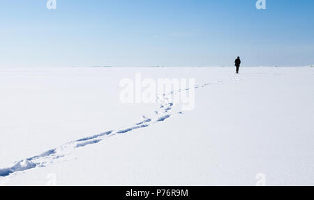 Footsteps of lonely person walking on frozen sea covered with snow - Stock Photo