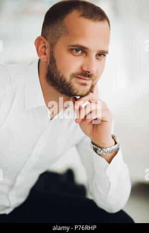 Confident man holding chin by hand and looking at camera. - Stock Photo