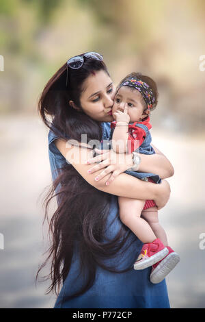 5 month cute baby girl in arm of her mother in the park. - Stock Photo