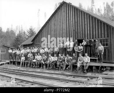 . English: Crew posing at camp behind railroad tracks, Beaver Creek Logging Company, Vernonia, ca. 1922 . English: This company probably operated in Vernonia, Oregon with headquarters in Portland and became the Connacher Logging Company in 1925. Caption on image: Beaver Creek Log Col, No. 858 PH Coll 516.60 Subjects (LCSH): xyz  . circa 1922 3 Crew posing at camp behind railroad tracks, Beaver Creek Logging Company, Vernonia, ca 1922 (KINSEY 2086) - Stock Photo