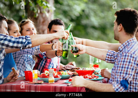 Group of happy people eating food outdoors - Stock Photo