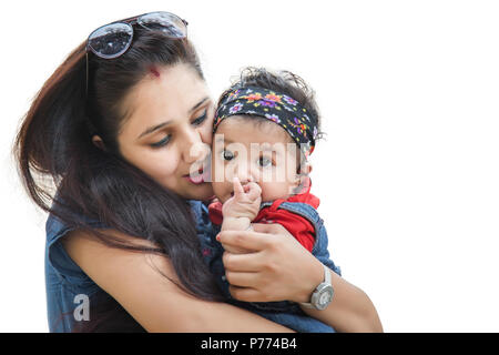 Happy Indian mother kissing her 5 month cute daughter isolated on white background. - Stock Photo