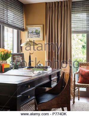 Writing desk at window with antique chair and lamp. - Stock Photo