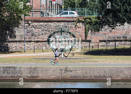 two joggers in front of the equatorial sundial on the river bank, frankfurt am main, germany - Stock Photo