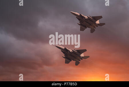 US Air Force McDonnell Douglas, two USAF low flying F-15E Strike Eagles at sunset. High speed low flying fighter jet, with a beautiful orange glowing  - Stock Photo