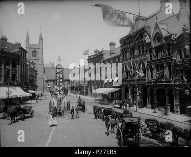 English: Market Place, Reading, looking northwards to St. Laurence's Church, 1887. The Simeon Obelisk, designed by Sir John Soane, is garlanded to celebrate the Golden Jubilee of Queen Victoria. On the west side, Nos. 33 and 34 (J. S. Salmon and Son, tea dealers). On the east side, Nos. 21 and 20 (the Royal Standard Inn); Nos. 19 and 18 (the Elephant Inn); No. 17 (Frank Cooksey, estate agent); Nos. 16, 15, 14 and 13 (London and County Bank); Nos. 12 and 11 (Morris and Davis, tailors); No. 8 (Sutton and Sons, seedsmen); No. 7 (the 'Reading Mercury' office); No. 6 (George Russell Butler, estate  - Stock Photo