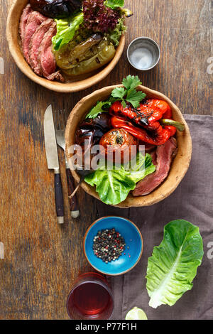 Grilled steak and grilled vegetables served in bread plate on wooden table, top view - Stock Photo