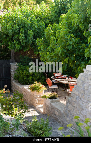 Table and chairs on rustic patio - Stock Photo