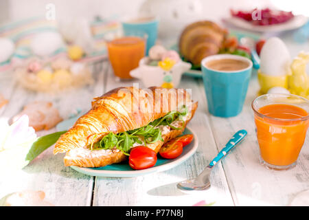 A family breakfast of croissants with rocket salad and cheese and aromatic coffee. Fresh tulips of pink color and eggs of different colors and Easter decor, ceramic rabbits. Free space for text. - Stock Photo
