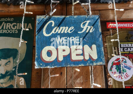 Old fashioned, retro, vintage 'come in we're open' faded, scratch sign board hanging on a pub, coffee shop window. Close up. - Stock Photo