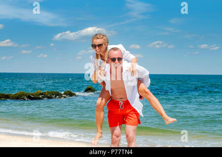 Happy couple in love on beach summer vacations. Young man giving piggyback ride to woman on beach. - Stock Photo