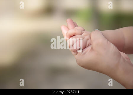 mother holding her baby hand close-up. - Stock Photo