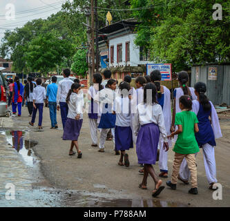 Bodhgaya, India - July 9, 2015. Highschool students walking on rural road in Bodhgaya, India. Bodh Gaya is the most revered of all Buddhist sacred sit - Stock Photo