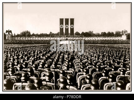Nuremberg 1930's Waffen SS troops wearing polished helmets in precise serried ranks standing at salute during a German Nazi rally pre-World War II with large Swastika banners dominating arena - Stock Photo