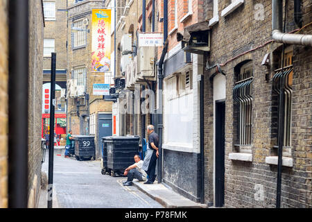 London, UK - June 22, 2018 - Restaurant staff having a break on the back street of London Chinatown - Stock Photo