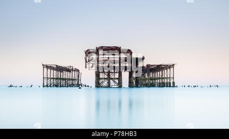 Minimalistic West Pier in Brighton, East Sussex, at sunrise and reflected in a calm sea with beautiful pastel shades in a cloudless sky - Stock Photo