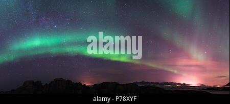 Aurora borealis above the mountains with milky way at Lofoten - Norway - Stock Photo