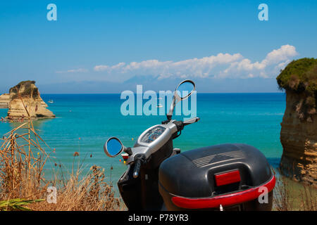 motor scooter, motorbike parked on the beautiful coast with amazing view to azure lagoon, gulf.Active summer holiday concept. Rent any transport on your vacation.Scooter on the beach - Stock Photo