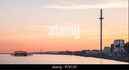 British Airways i360 and West Pier, Brighton, East Sussex, including the seafront at sunset with intense orange and yellow sky - Stock Photo
