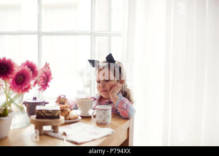 A little girl at the table is eating breakfast by the window. Good morning. Copy space - Stock Photo