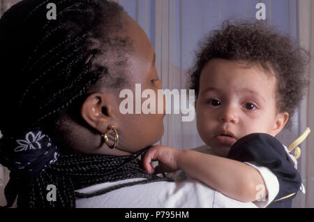 Black mother holding her unhappy mixed race baby girl - Stock Photo