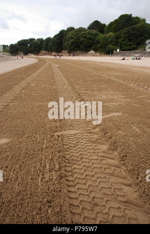 Tyre marks in the sand after a tractor has cleaned to beach at Barry Island, south Wales - Stock Photo