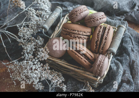 Freshly baked macaroons in wicker basket with handles with small white flowers on wooden background. Selective focus. - Stock Photo