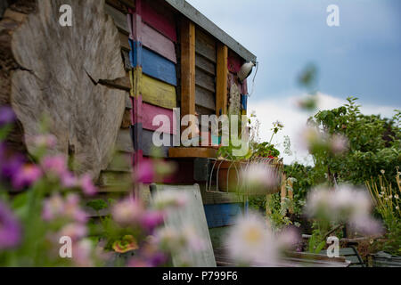 A beautiful decorated shed painted in pastel stripes situated in a relaxing garden. - Stock Photo