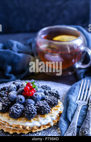 homemade waffles with blueberries and blackberries, powdered sugar on a stone plate with fruit. Shallow depth of field. - Stock Photo