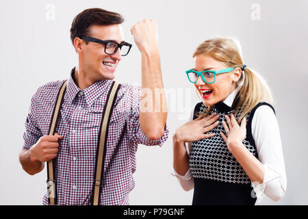 Nerdy man is showing to nerdy girl how strong he is. - Stock Photo