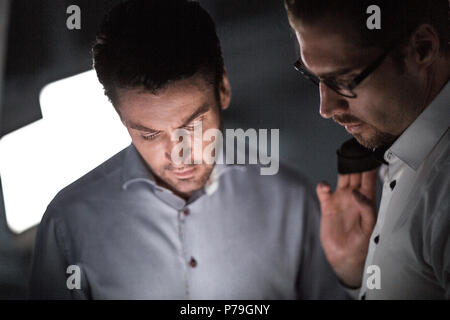 close up.two business men in the workplace in the evening - Stock Photo