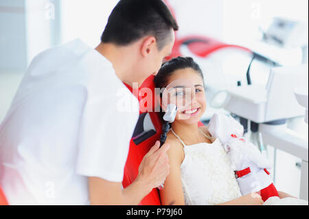 Beautiful smile with white teeth. A dentist examines the oral cavity of a young beautiful girl through a magnifying glass in the dental office. - Stock Photo