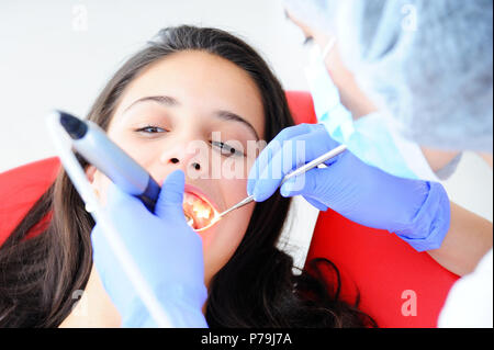 Young beautiful girl in dental office. Children's dentist examines teeth to a child. - Stock Photo