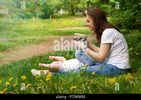 Young pregnant girl sits on lawn in city park. Mother plays with her son. Little boy is lying on lawn. Blur effect - Stock Photo