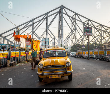 May 27,2018. Kolkata, india. A yellow Taxi parked on the Howrah Railway station overlooking the Howrah Bridge behind. - Stock Photo