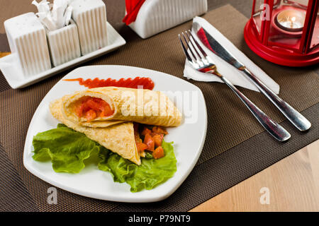 ceramic white plate with salad  and omelette stuffed vegetables, on table in restaurant - Stock Photo