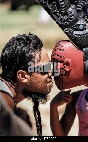 Maori man performs hongi with front of Ngātokimatawhaorua ceremonial war canoe (waka taua) at the Waitangi treaty grounds in New Zealand - Stock Photo