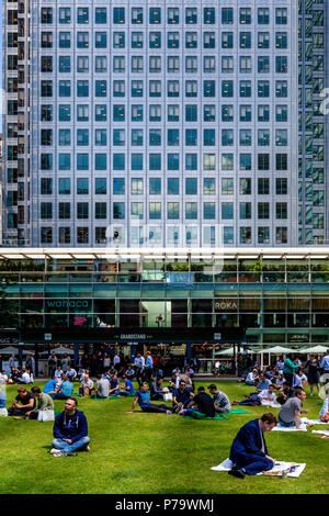 Office Workers Sitting On The Grass Eating Lunch, Canary Wharf, London, United Kingdom - Stock Photo