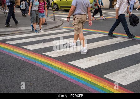 Paris, France - 24 June 2018: Gay pride flag crosswalk in Paris gay village with people crossing - Stock Photo