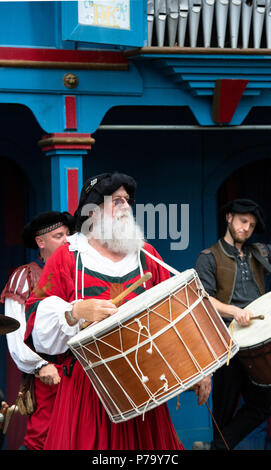 Drummer and group performing with drums at the Renaissance Festival, Maryland. The large drum hangs from the neck of Medieval reenactor in red outfit. - Stock Photo