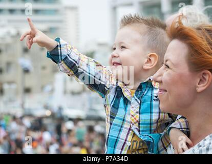 Adorable child and his mother watching the air show dedicated to Israel's Independence Day in the Tel Aviv promenade. Yom Ha'Atzmaut stock image. - Stock Photo