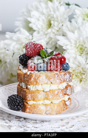 Homemade cake with ricotta and fresh berries-raspberries, red currants, blueberries and blackberries with mint and powdered sugar. Selective focus - Stock Photo