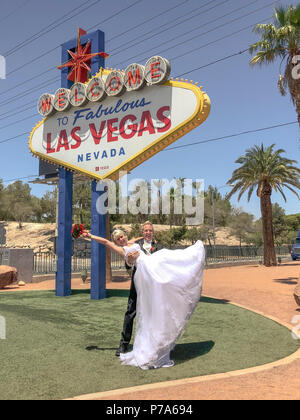 Bride and groom at Welcome to Fabulous Las Vegas sign. Newlywed couple pose for photo, the bridegroom lifting up the bride with bouquet in his arms. - Stock Photo