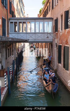 Gondolas with tourists in Rio del Vin, Castello, Venice, Veneto, Italy passing under the covered pedestrian bridge between buildings of the Danieli H - Stock Photo